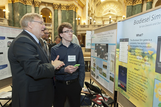 State Senator Van Wanggaard learns the Biodiesel Sim game from UW-Parkside student Kyle Zawacki (r)