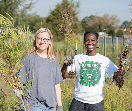 Two female Parkside students pulling weeds at Garden of Eatin