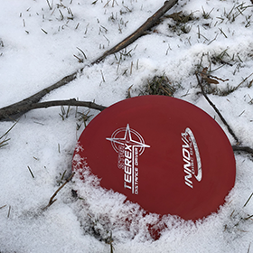 Red disc golf disc in the snow