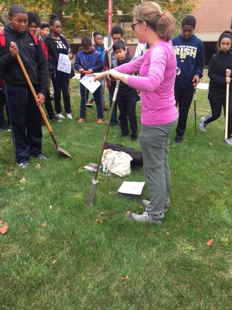 Laura Schulz showing students how to dig into the ground.